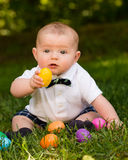 Infant baby boy playing with Easter eggs. Cute infant baby boy playing with Easter eggs Royalty Free Stock Photography