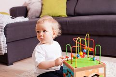 Infant baby boy playing indoors with toy sitting on soft carpet. Infant baby boy playing indoors with labirint toy sitting on a light soft carpet royalty free stock images
