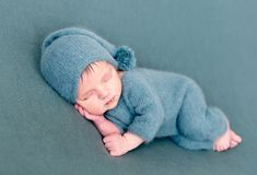 Infant baby boy sleeping in woolen costume with bare feet. On blue blanket. Dreamy little child sleeps Royalty Free Stock Image