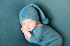 Infant baby boy sleeping in woolen costume with bare feet. On blue blanket. Dreamy little child sleeps Royalty Free Stock Images
