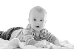 Infant baby boy smiling on a white blanket isolated on white bac Royalty Free Stock Image