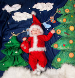 Infant baby boy wearing Santa costume holding bag with gifts. Royalty Free Stock Photography