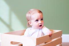 Infant baby boy in wooden crate in studio Stock Photos