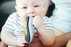 Infant Baby Child Boy Six Months Old is Takes his Shoe in the Mouth. Little Baby Child Boy Six Months Old is Takes his Shoe in the Mouth stock photo