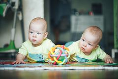 Infant Baby Child Twins Brothers Six Months Old is Playing on the Floor. Little Baby Child Twins Brothers Six Months Old is Playing on the Floor royalty free stock image