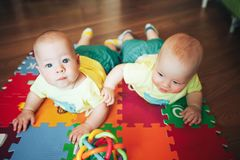 Infant Baby Child Twins Brothers Six Months Old is Playing on the Floor. Little Baby Child Twins Brothers Six Months Old is Playing on the Floor stock photo