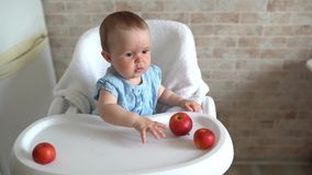 Infant baby eating apple. Cute little girl eating and playing apples in high chair. Adorable child tasting fruit. Healthy eating c. Hildren. Kid enjoy fresh stock video footage