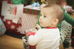 Infant Baby Enjoying Christmas Morning Near The Tree Royalty Free Stock Image