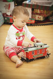 Infant Baby Enjoying Christmas Morning Near The Tree Royalty Free Stock Photo