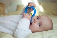 Infant baby girl in bed playing with rattle Stock Photography
