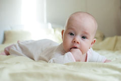 Infant baby girl in bed Royalty Free Stock Image
