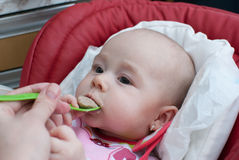 Infant baby girl in children chair eating meal Royalty Free Stock Images