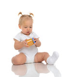 Infant Baby girl kid sitting and holdingin hands jar of child ma Royalty Free Stock Photography