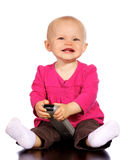 Infant baby girl playing with t.v. remote Royalty Free Stock Photos