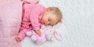 Infant baby girl sleeping on bed Stock Images