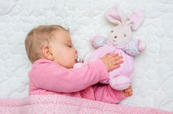 Infant baby girl sleeping on bed Stock Image