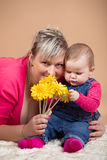 Infant baby with his mom and yellow flowers Royalty Free Stock Photos
