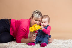 Infant baby with his mom and yellow flowers Royalty Free Stock Image