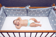Infant baby laying in decorated cot. Little beautiful infant baby laying in decorated cot Royalty Free Stock Photo