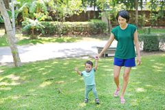 Infant baby learning to walk with his mother on the green grass. First steps stock image