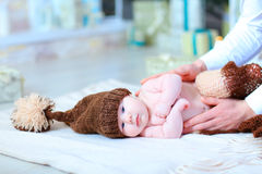 Infant baby lying on blanket in hat with bubo. Baby lying on blanket and looking at camera. Child wrapped in brown blanket and dressed in hat with bubo. Concept Royalty Free Stock Images