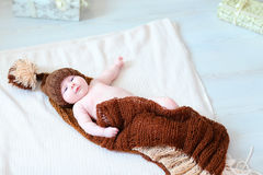 Infant baby lying on blanket in hat with bubo. Newborn cute baby lying on blanket. Child wrapped in brown blanket and dressed in knit hat with bubo. Concept of Royalty Free Stock Images