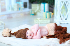 Infant baby lying on blanket in hat with bubo. Newborn cute baby lying on blanket and looking at camera. Child wrapped in brown blanket and dressed in hat with Royalty Free Stock Photography