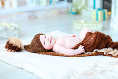 Infant baby lying on blanket in hat with bubo. Newborn cute baby lying on blanket and looking at camera. Child wrapped in brown blanket and dressed in knit hat Royalty Free Stock Image