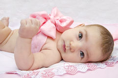 Infant baby with a pink bow. Baby with a bow on pink background Royalty Free Stock Images