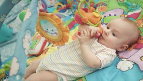 Infant baby playing on colorful mat. Close up of cute baby boy play with toy