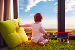 Infant baby sitting on carpet at home and watches the beautiful cityscape through the window Stock Photo