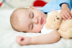 Infant baby sleeping with plush toy Stock Photos