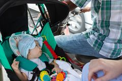 Infant baby in stroller seat in the motorcycle cradle. Unsafety concept. Danger riding. Asian taxi.  royalty free stock images