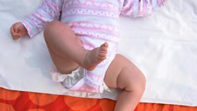 Infant baby in suit lying on her back. stock video footage