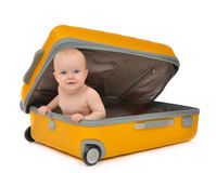 Infant baby toddler sitting in yellow plastic bag. Happy infant baby toddler sitting in yellow plastic travel suitcase on wheels getting ready for vacation Stock Photo