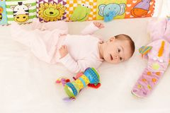 Infant with baby toys. Infant girl lying on back surrounded with colorful baby toys Stock Photography