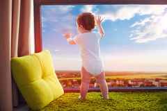 Infant baby watching the beautiful valley cityscape through the window at home Stock Photography