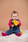Infant baby with yellow flowers Stock Photos