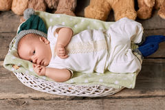 Infant in basket, wooden background. Royalty Free Stock Images