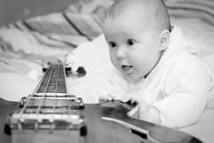 Infant and the bass guitar Royalty Free Stock Photography