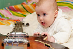 Infant and the bass guitar royalty free stock photos