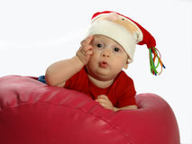 Infant on bean bag wearing a hat. Infant laying on a red bean bag with a christmas hat on Royalty Free Stock Photo