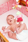 Infant in the bed. Little happy infant in a pink bed Stock Photo