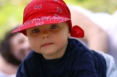 Infant with blue eyes. Baby infant with big blue eyes  in red hat Stock Images