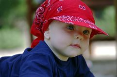 Infant with blue eyes. Baby infant with big blue eyes  in red hat Royalty Free Stock Photo