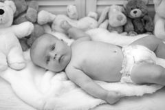 Infant with blue eyes and curious face on light blanket. With toys on background, defocused. Baby boy in diaper and his white teddy bear. Childhood and stock image