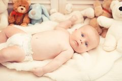 Infant with blue eyes and curious face on light blanket. With toys on background, defocused. Baby boy in diaper and his white teddy bear. Childhood and royalty free stock images