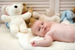 Infant with blue eyes and surprised face on light blanket. With toys on background, defocused. Baby boy and his white teddy bear. Baby lying on white duvet stock image