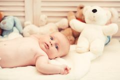 Infant with blue eyes and surprised face on light blanket. With toys on background, defocused. Baby boy and his white teddy bear. Baby lying on white duvet stock images