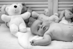 Infant with blue eyes and surprised face on light blanket. With toys on background, defocused. Baby boy and his white teddy bear. Baby lying on white duvet stock photos